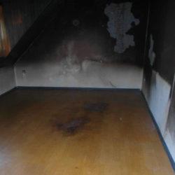 Entrümpelung: leergeräumter Raum mit Flecken auf Boden und an Wänden
